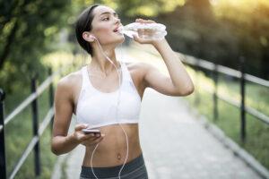 mulher praticando exercício e bebendo aguar