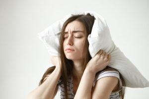 Mulher com insónia com o travesseiro abraçando sua cabeça