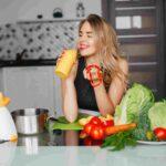 mulher de vestido comendo verduras e legumes sobre um balcão