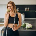 Mulher com roupas de academia, comendo fruta e segurando fita métrica