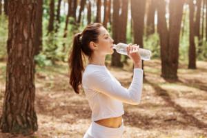Close em mulher bebendo água com roupas esportivas em parque
